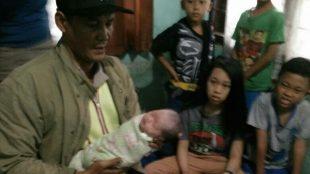 Petugas Kepolisian menggendong bayi perempuan yang ditemukan oleh warga Kelurahan Pabuaran, Cibinong, dalam keadaan hidup. (dok. KM)