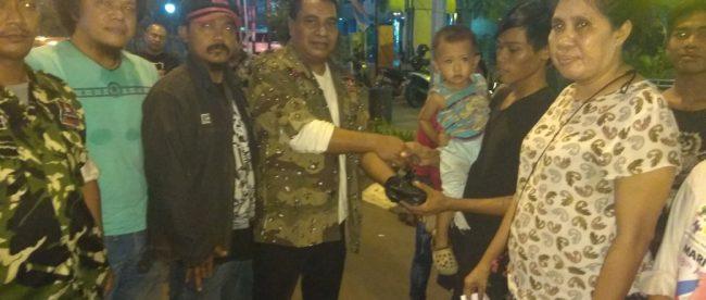 Ketua GRIB Kota Bekasi membagikan nasi bungkus kepada warga saat