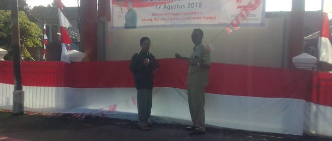 Kades Sukaharja, Cijeruk, Kabupaten Bogor, Santoso, saat memasang atribut bendera di halaman kantor desanya (dok. KM)