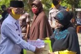 Bupati Pelalawan HM Harris (kiri) menyerahkan BLT ke salah satu warga Desa Sido Mukti, Kamis 4/6/2020 (dok. KM)