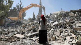 Seorang wanita Palestina menyaksikan alat berat milik otoritas Israel menghancurkan bangunan di wilayah Tepi barat Terjajah