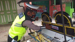"""Personil Satlantas Polres Tanjungbalai menempelkan stiker """"AYO PAKAI MASKER"""" (dok. KM)"""