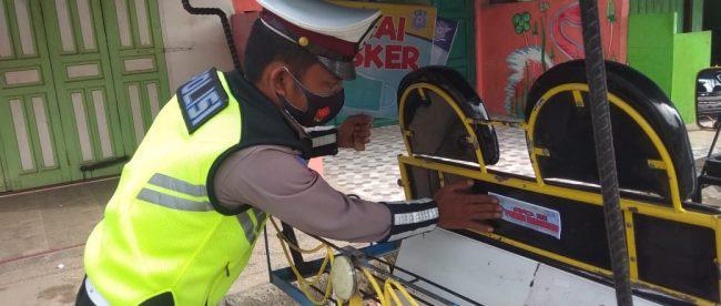 Personil Satlantas Polres Tanjungbalai menempelkan stiker